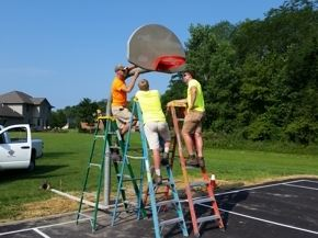 Three Men Installing a Basketball Hoop